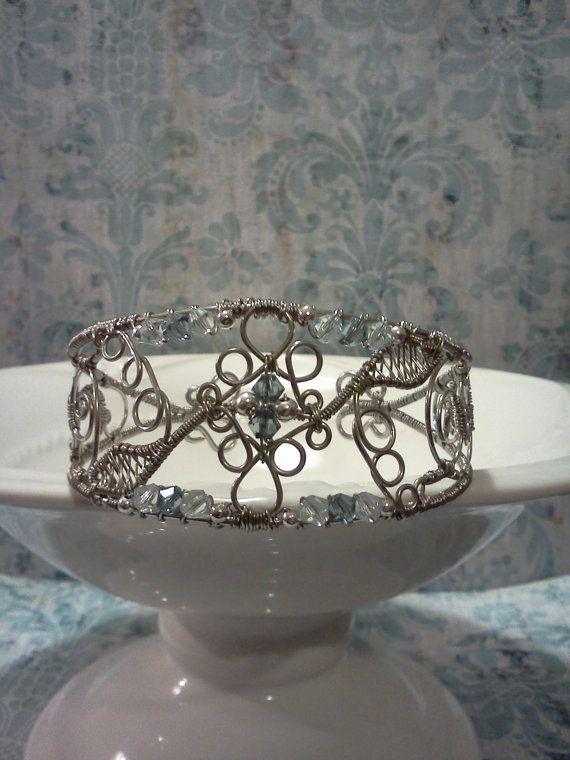 Filigree inspired cuff bracelet using tarnish resistant silver colored wire and shades of blue bicone swarovski crystals. This cuff measures