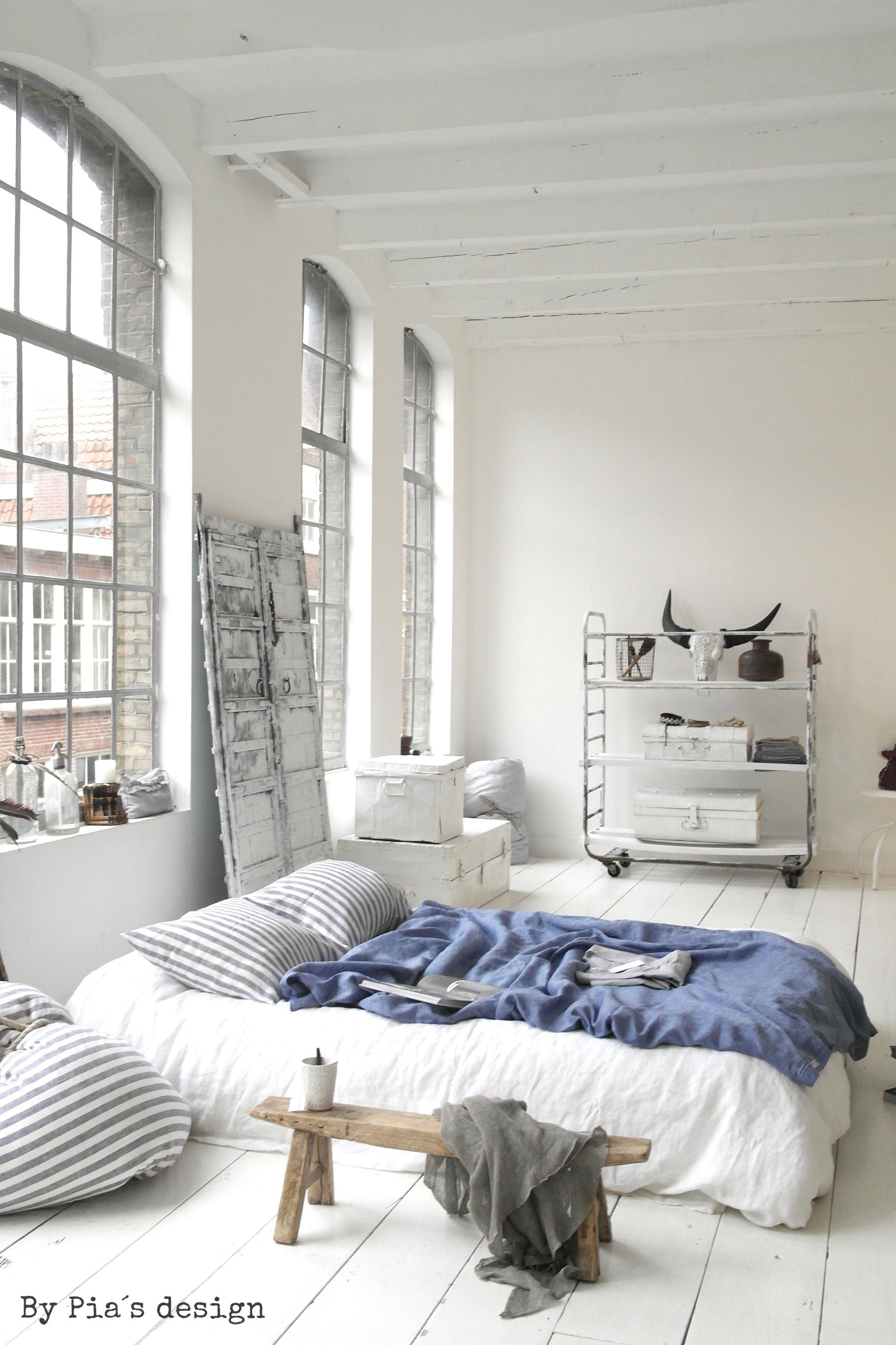 All White Minimalistic Bedroom With Bed On The Floor Natural Light Big Windows Blue Blanket Accent Minimalism Interior Bedroom Design Minimalist Bedroom
