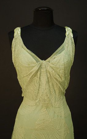 "WORTH NET EVENING GOWN with SEASHELL DESIGN, c. 1932. Sleeveless pale seafoam green V-neck decorated with large shells of various types, the straps with iridescent sequin decoration and scattered rhinestones at shoulder and down low back, attached seafoam crepe de chine slip, side closure. Label ""Worth"". Belonged to Elizabeth Arden, purchased from employee who received dress as a bequest at Arden's death. Detail"