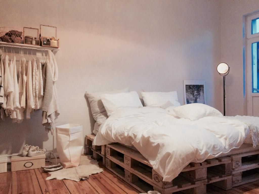 Schönes Bett aus Paletten, Kleiderstange und gemütliche