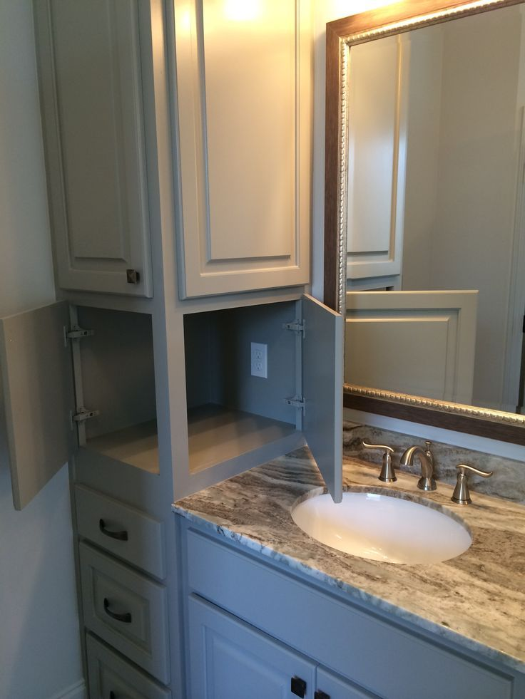 Bathroom cabinets with hidden electrical plug. Dual doors so you don't have to dig in the back of th