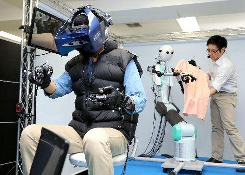 ロボットの指先から送られてきた布の感触を、特殊な手袋を通して確かめる研究者(左)=11日午前、横浜市港北区、遠藤啓生撮影