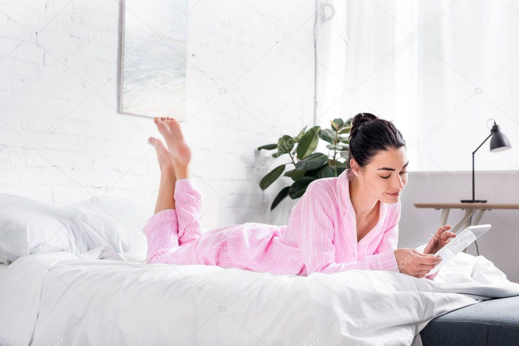 Side View Smiling Woman Pajamas Using Tablet While Lying Bed