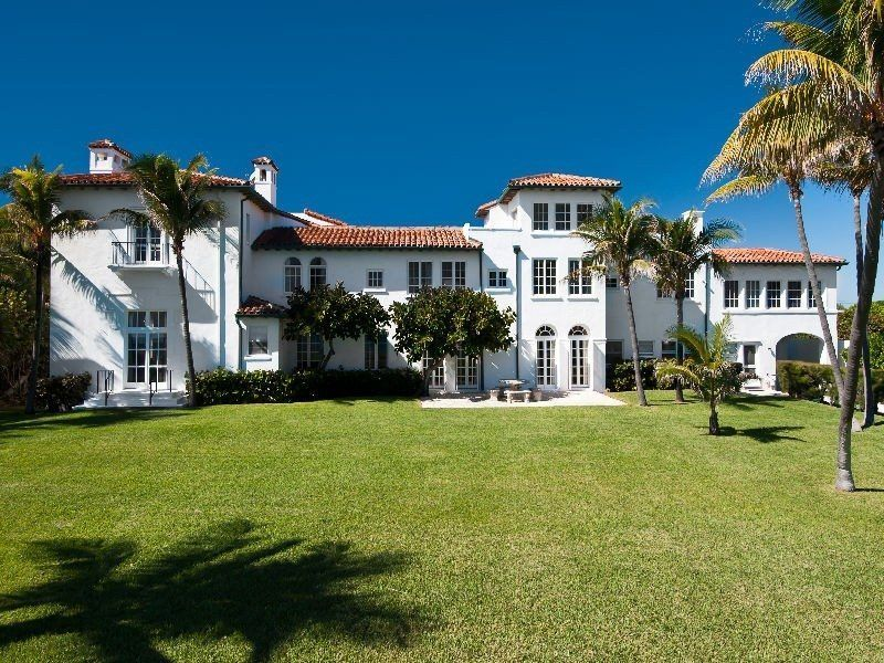 This Historic Palm Beach Mansion Has White Stucco Walls Red Spanish Tile Roofing Arched Openings Trim A Stone Patio Balconies Multiple Chimneys