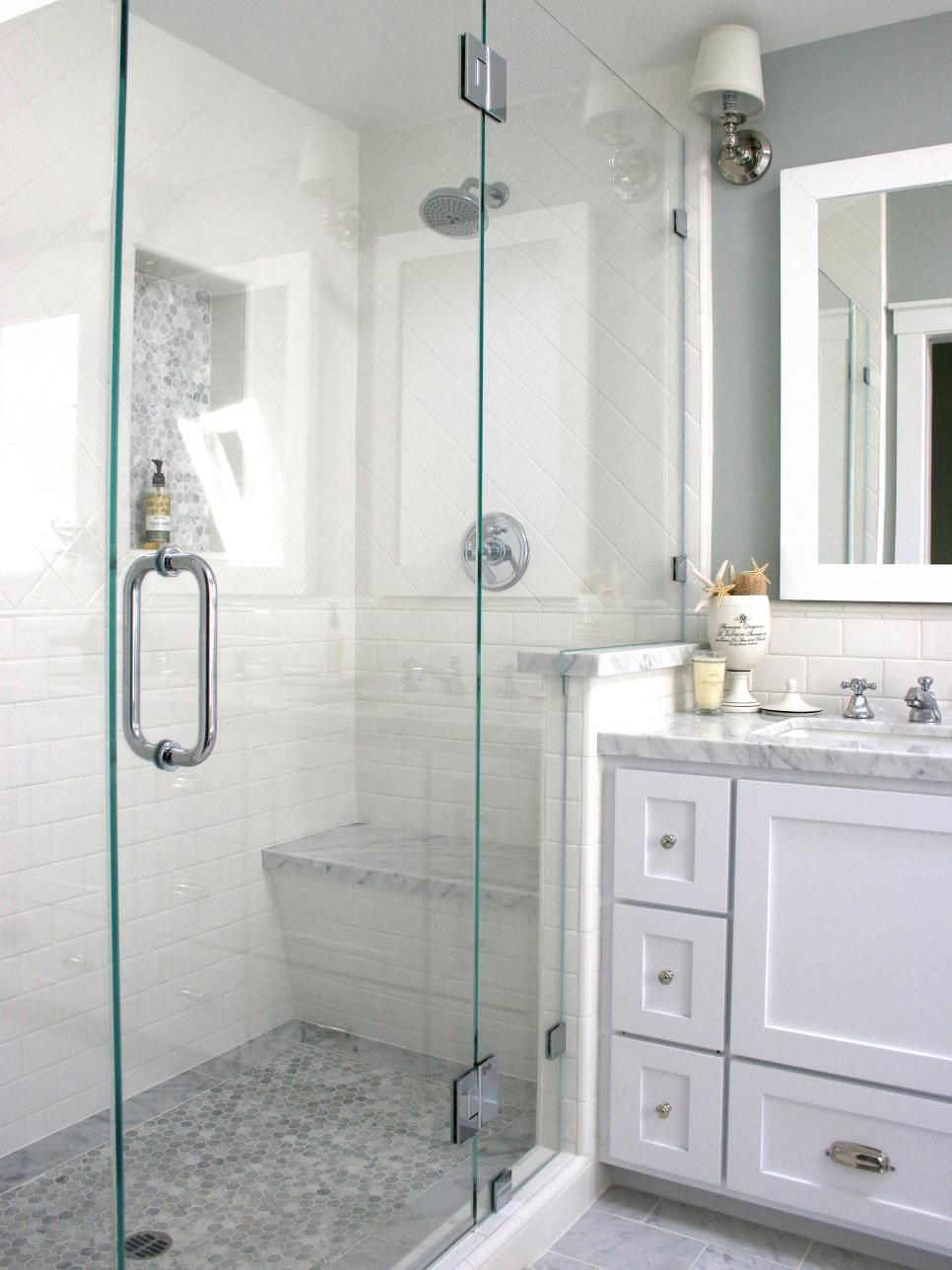 A glassenclosed shower with white tile walls and a gray mosaic tile
