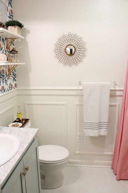 Photo of Bathroom with wallpaper, gold fixture, gold knobs, marble countertop, white shel…