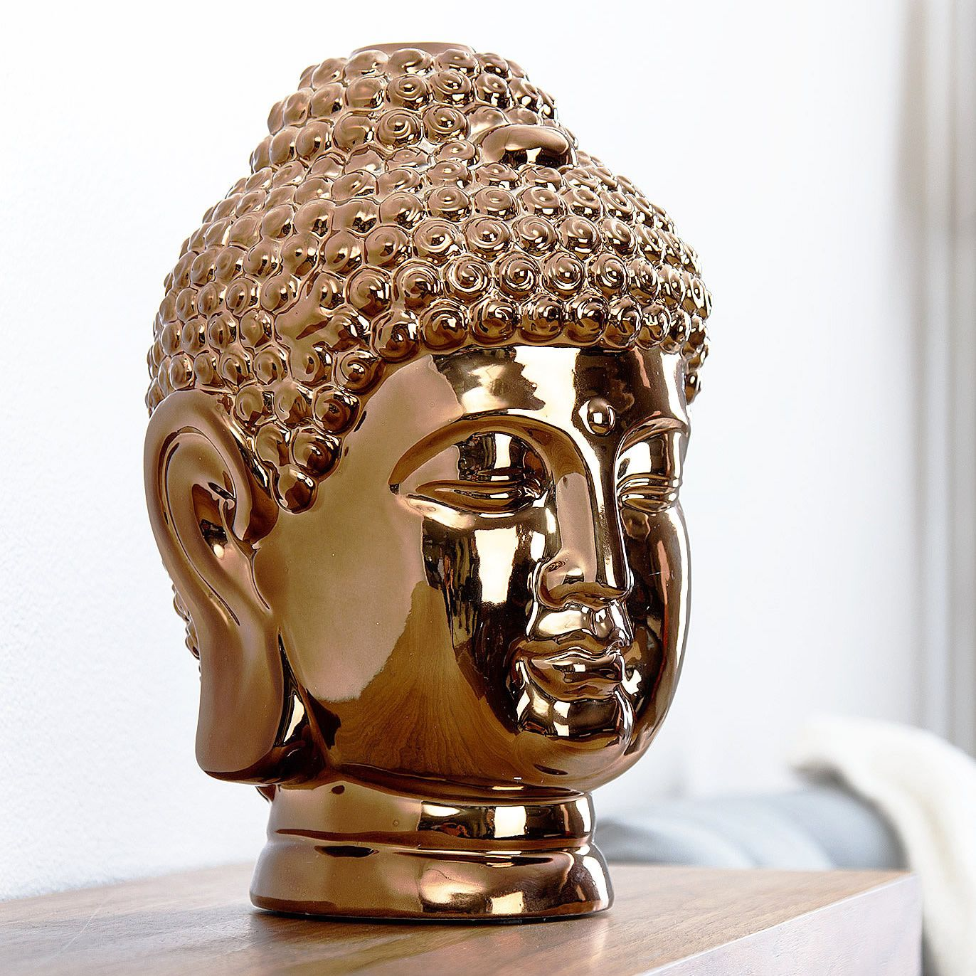 this ceramic buddha head statue finished in gold chrome brings a