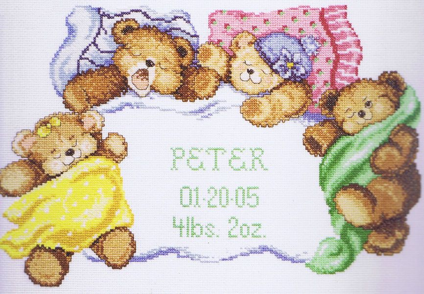 A family of teddy bears settle down to sleep in this pretty birth announcement.