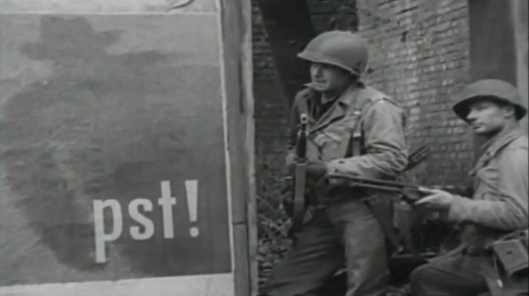 GIs during street fighting en route to Berlin, April 1945. Note the poster on the wall warning civilians to beware of spies. The GI in the foreground carries the Browning Automatic Rifle (BAR) the standard squad automatic weapon at the time.