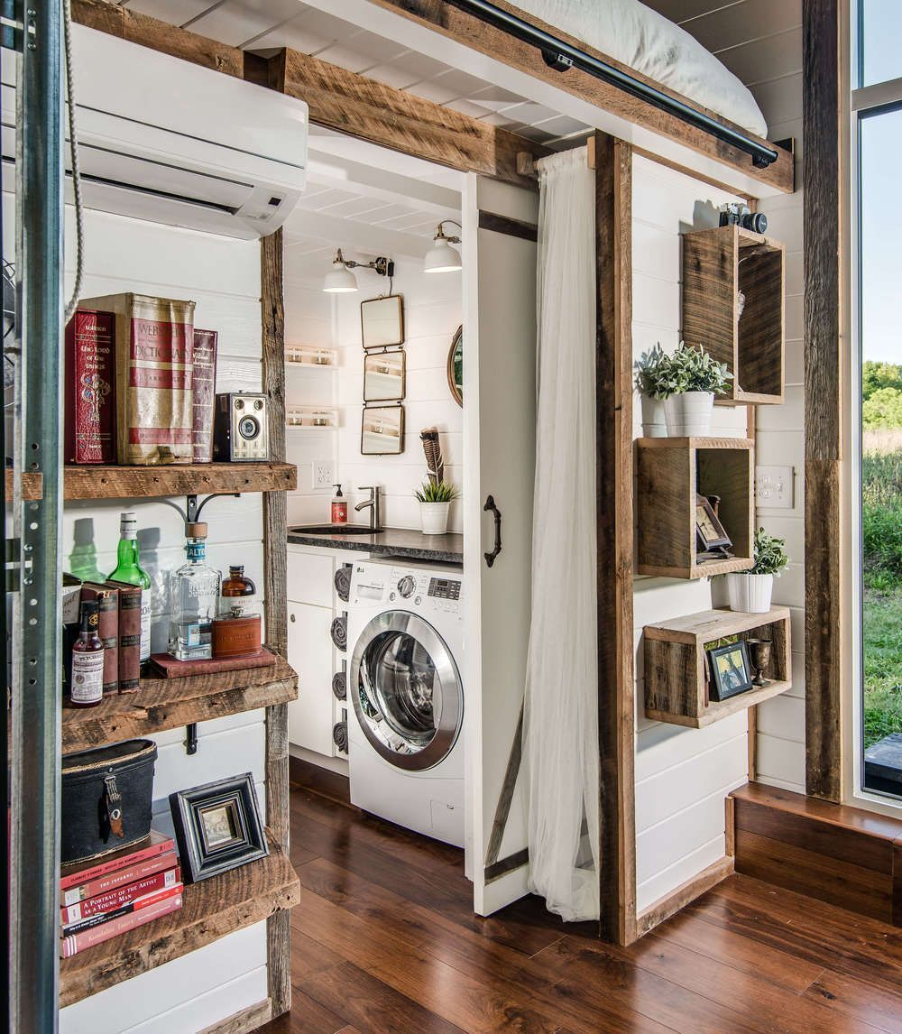 Tiny house interior with lofted bed storage and laundry