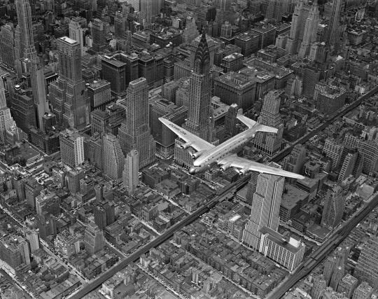 Aerial view of a DC-4 passenger plane flying over midtown Manhattan, 1939