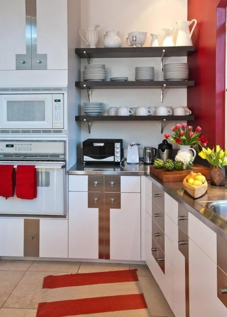 Modern kitchen with white cabinetry with stainless steel detail.  Open dark shelving.  Stainless Steel countertop
