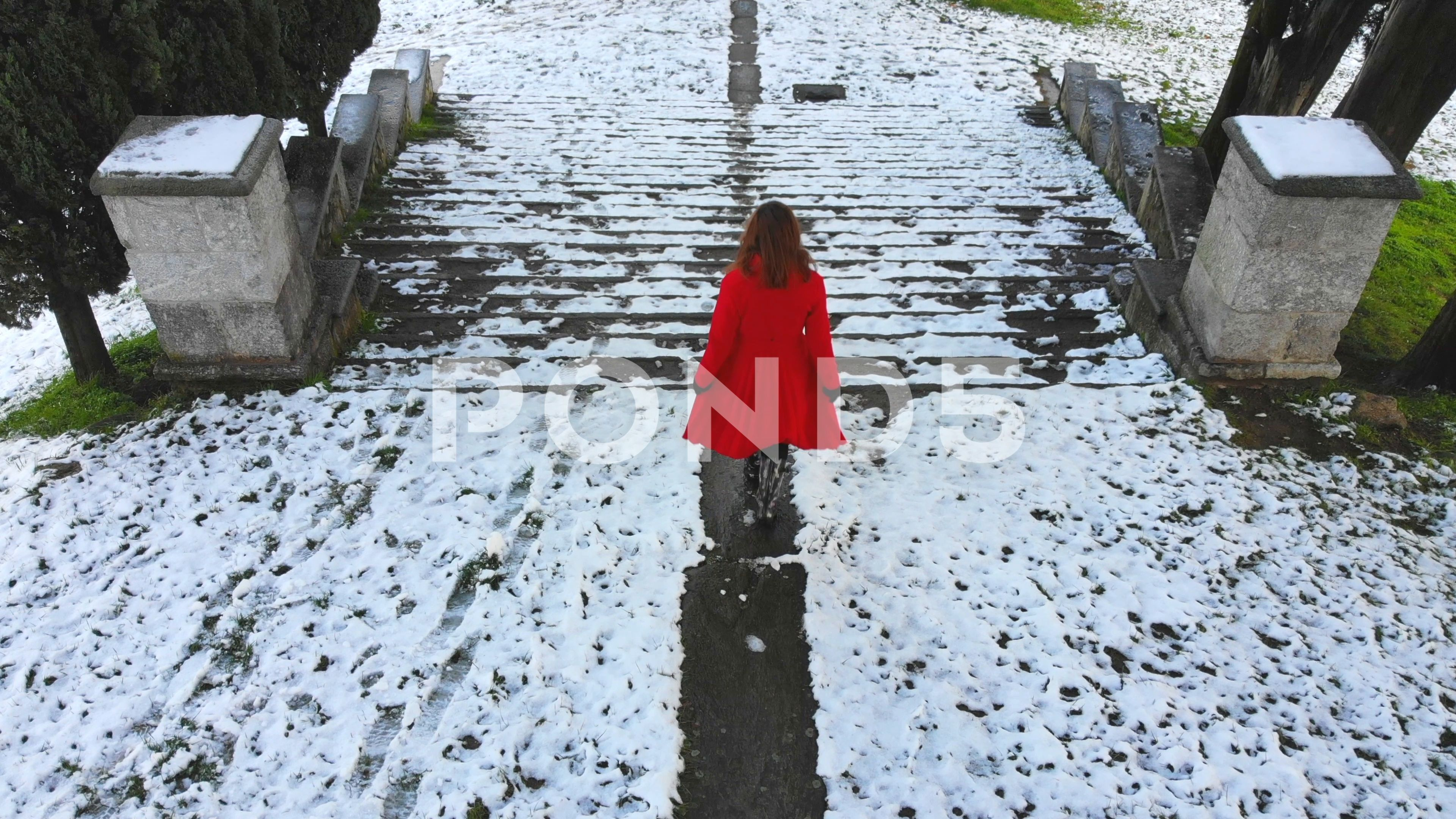 The Woman In The Red Coat Goes Down An Ancient Staircase Stock