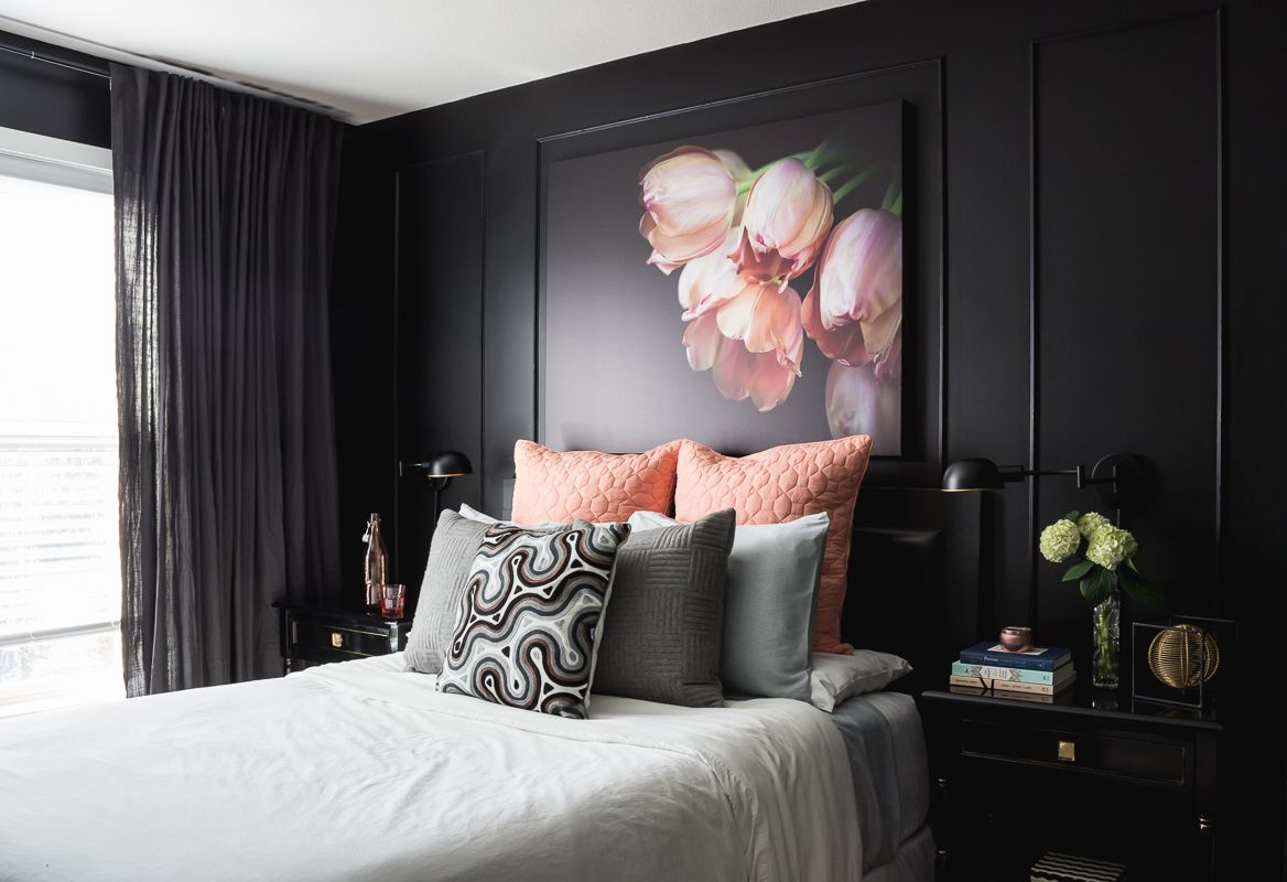 Black walls, oversized floral art and pink accessories in a ...