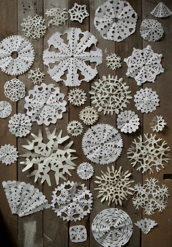 Paper snowflakes decorate window with some paper