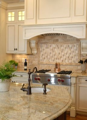 Dreamy kitchen with sand colored countertops and tumbled marble