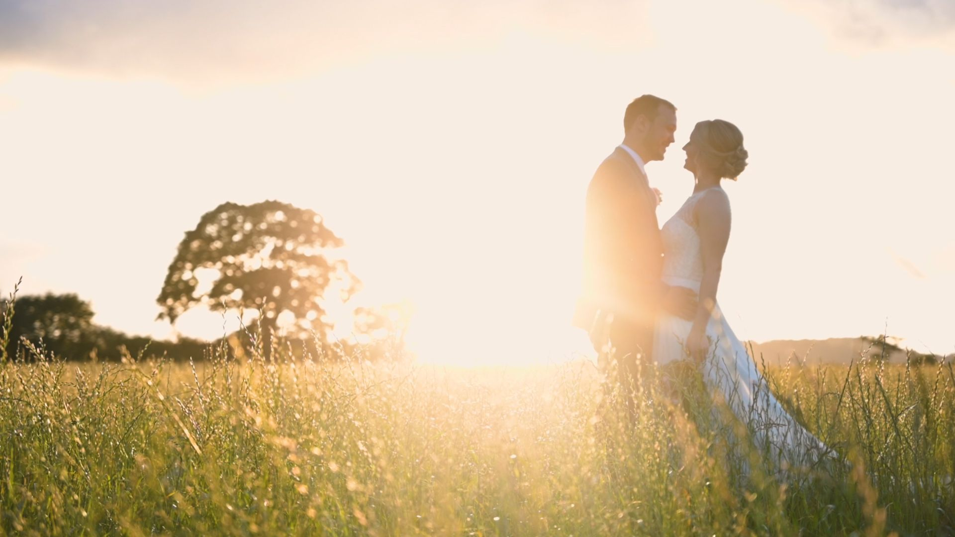 Bride and groom in each others arms in a field at sunset