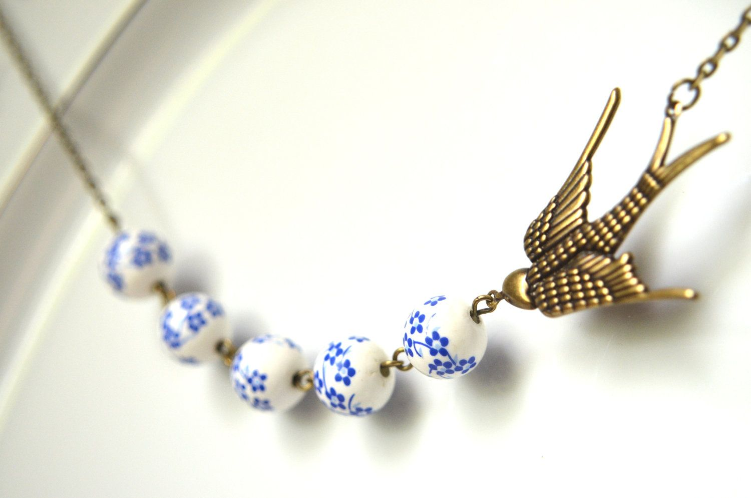 White & Blue Bird Necklace - Sparrow, Antique Brass, Like Polish Pottery, Porcelain, Ceramic, Diving Swallow. $18.00, via Etsy.