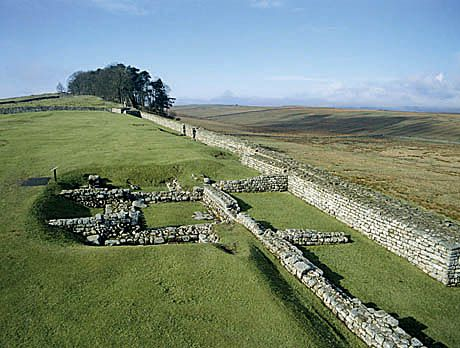 View west along the north curtain wall of Housesteads Roman Fort, which follows the line of Hadrian's Wall, laid down before the building of the fort. In the centre are the remains of one of the turrets on the Wall, which is partly overlain by a later fort building.