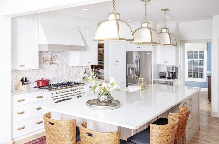 Bright white #cabinetry paired with brass fixtures and fittings. This beautiful kitchen inspires us to put on our aprons and start cooking. Who else loves an all-white #kitchen?!  #designsthatinspire   Inspired By: Triton Stone Group  #whitekitchen #allwhitekitchen #whiteandbrass #brasslighting #kitchenislanddesign #kitchenisland #islandlighting #whiterangehood #rangehood #rangehooddesign #kitchendesign #kitchens #kitcheninspiration
