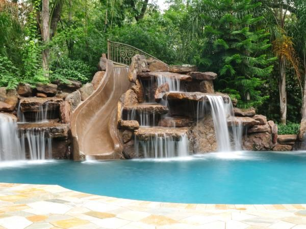 swimming pool waterfall pool slide it looks natural with the mountains behind it by lisa sands xiozh - Swimming Pools With Waterfalls