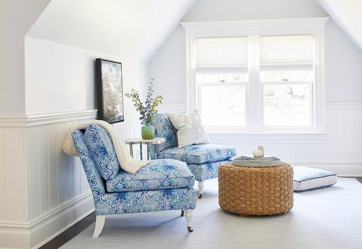 Blue and white attic bedroom living space boasts two blue slipper chairs placed on a gray rug on either side of a quatrefoil accent table placed in front of a framed painting mounted on a white wall above shiplap trim.