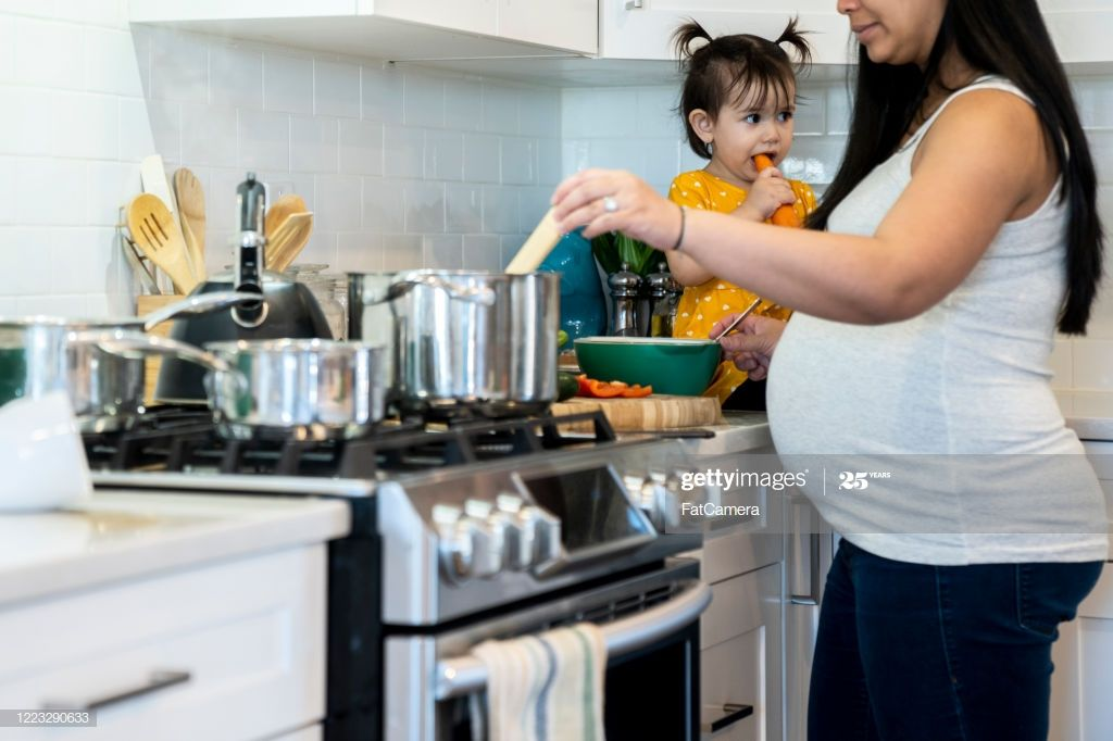 Multitasking Pregnant Mom Cooking In The Kitchen With Young Daughter Cooking Kitchen Cooking Photography Mom Cooking