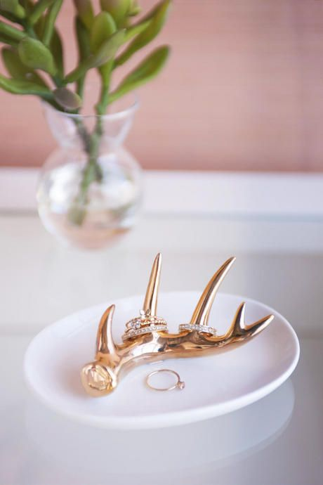 A gold metallic antler lays pristinely in this ceramic ring dish
