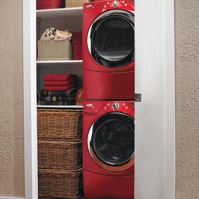 laundry room hidden in hall closet with stackable washer and dryer