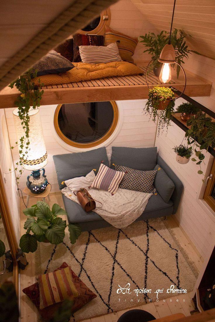 Das Wohnzimmer hat zwei runde Fenster. Das größere Fenster ...