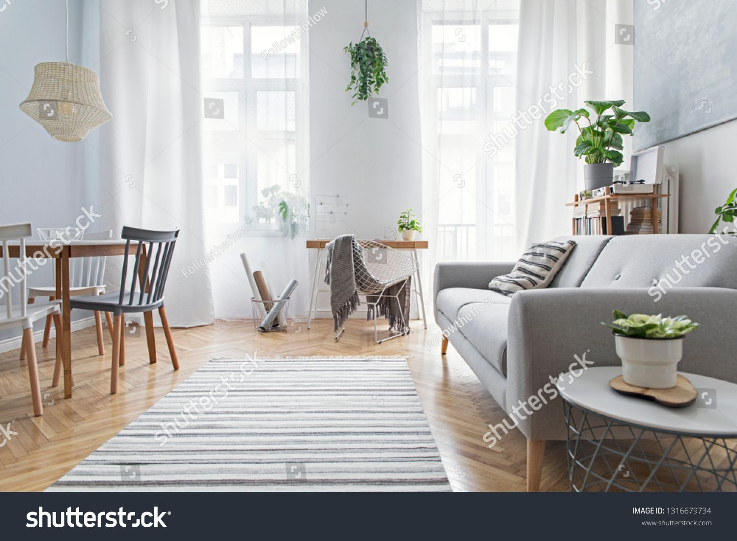 Modern scandinavian living room with design furniture family table plants bamboo bookstand and wooden desk Brown wooden parquet Abstract painting on the white wall Nice a...