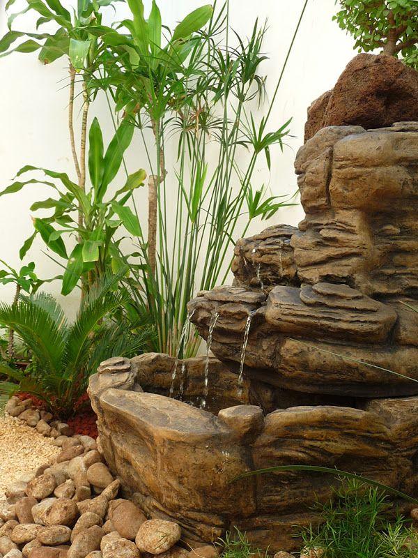 Modelo de fuente de agua sobre piedras con papirus al lado for Disenos de jardines para espacios pequenos