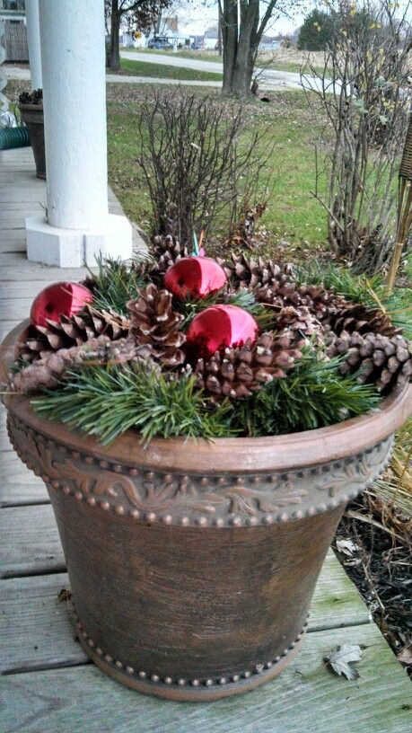Left the dirt in the flower pot.  Added cheap greenery on a rope.  My own pinecones and add a few bulbs by securing with floral sticks into the dirt to secure! #weihnachtsdekohauseingangaussen