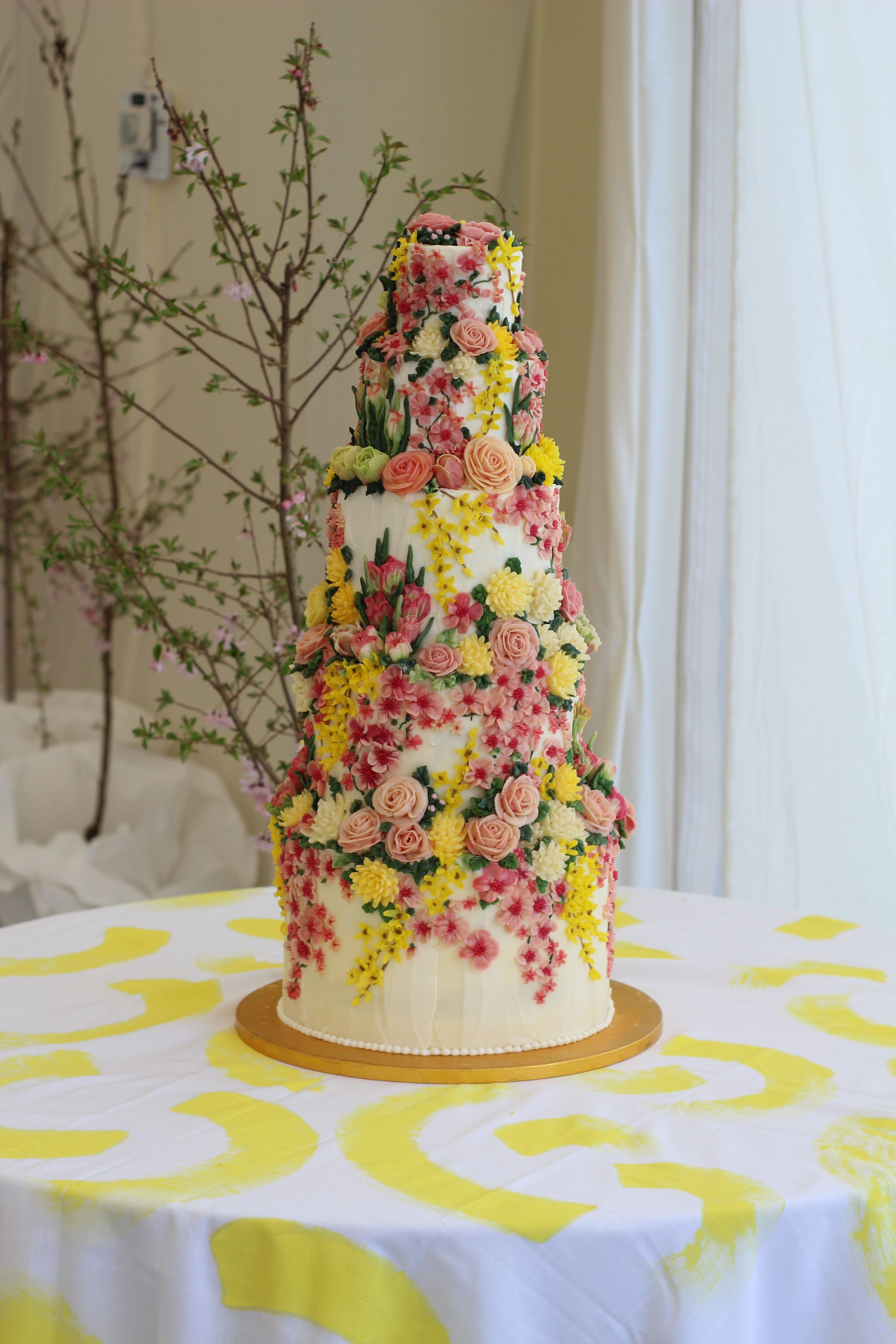 Huge buttercream wedding cake with piped spring flowers emma page
