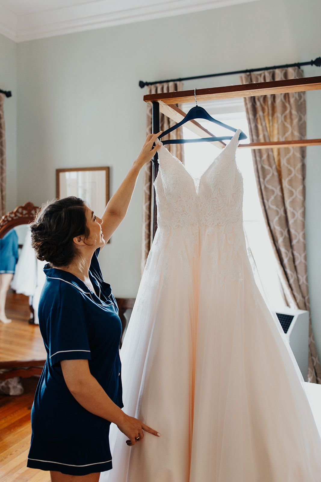 Sweet bride admiring her beautiful wedding dress hanging