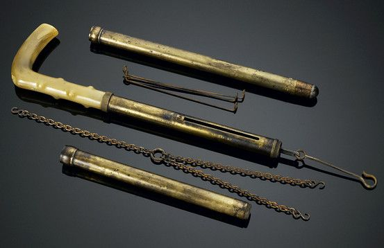 """Brass Scale Cane - This rare brass merchant's walking stick has a spring-loaded scale integrated into the shaft for weighing goods. The cane unscrews to reveal a hook with three chains that connect to a wire triangle, while a bar on the shaft slides to indicate the weight. A handsome, polished horn handle completes the rare cane.<br><br>35 1/2"""" length"""