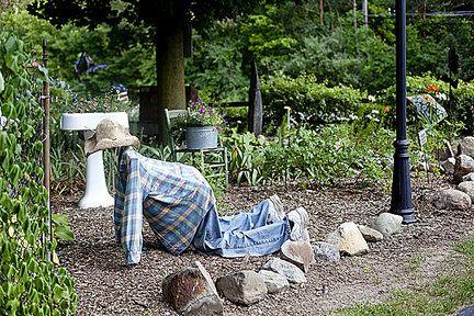 Garden art man crawling through the garden. Rough night or lost contact lens?
