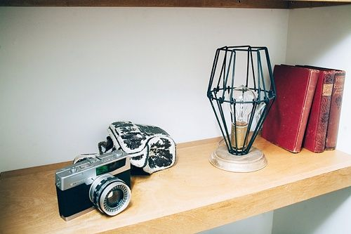 Our Vintage Camera and Vintage Books help accessorize this shelf alongside this cool industrial light by our friends at AFR.  Image by Jeffrey Ocampo