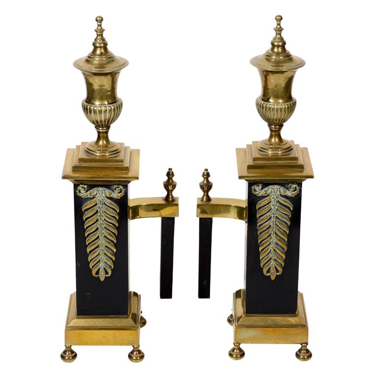 Pair of Neoclassical Brass Andirons with Stylized Urn Design  American  circa 1940  Pair of elegant footed andirons in brass with black enameled centers. The andirons have an exquisite neoclassical design with stylized urns which rest on corinthian columns. Centers also have laurel leaf design and legs with inward curve design.