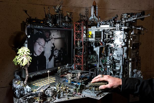 ドラム缶や壊れた兵器などが雑然と転がるビルの一角。戦闘後なのか、鉄骨や配管がむきだしだ。忙しく立ち回るカーキ色の軍服を着た兵士と護衛のロボット。秘密基地のワンシーンだが、俯瞰するとデスクトップパソコンとモニターという日常のデスクが現れる。ここは、第17回文化庁メディア芸術祭優秀賞を「プラモデルによる空想の具現化」で受賞した、新進気鋭のメディアアーティスト池内啓人が空想する世界だ。この驚異の作品はどうやって生まれたのか?