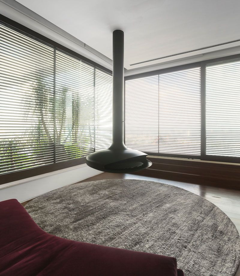 Fireplace Design circular fireplace : This lounge area surrounded by windows, has a hanging circular ...