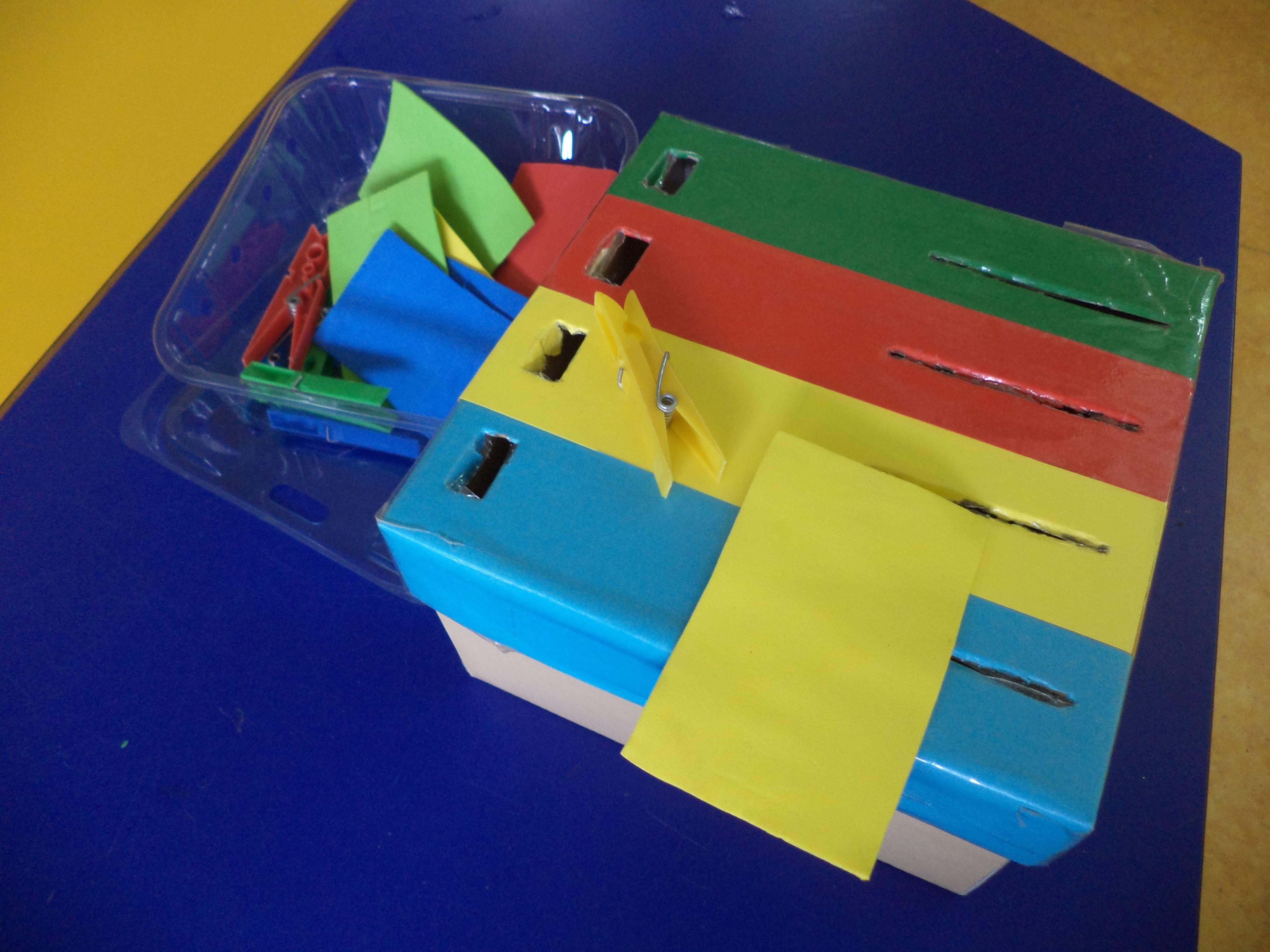capsa de cartró reciclada, paper eva i pinces. Posem la pinça i el paper eva al seu forat per colors. Treballem la motricitat fina i la concentració. Caja de cartón reciclada, goma eva y pinzas. Hay que poner la pinza y el cartón en su agujero correspondiente. Trabajamos la motricidad fina, discriminación de colores y la concentración.