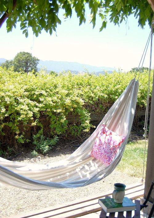 diy hammock..Make large hem  on each end of think fabric, string rope threw and hang with big screw in hooks.
