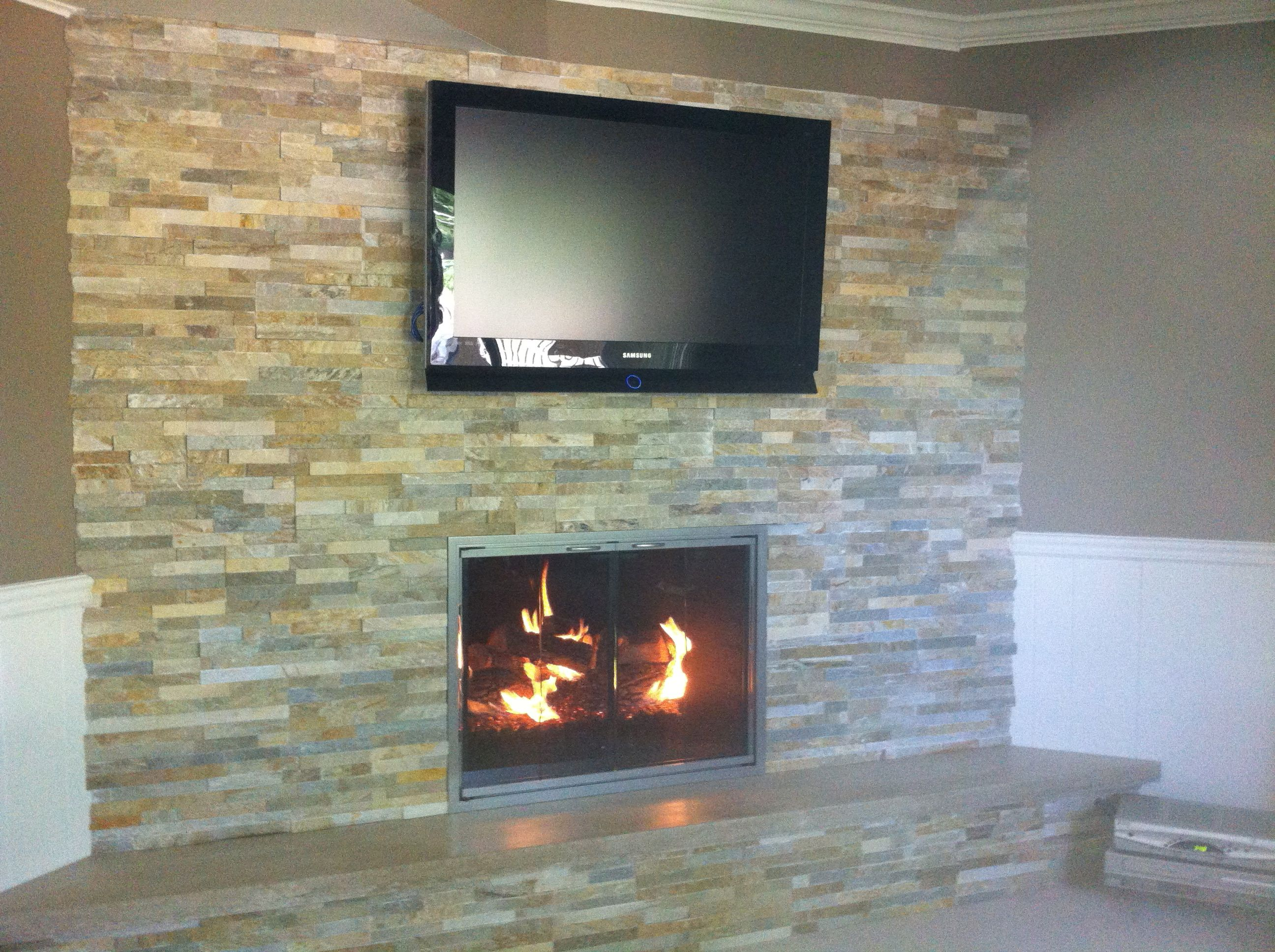 Gas Fireplace   Gas Logs by Rasmussen  Glass Door by Design Specialties  Ledgestone by Real Stone Systems  TV Above Fireplace  Sealed Limestone Hearth