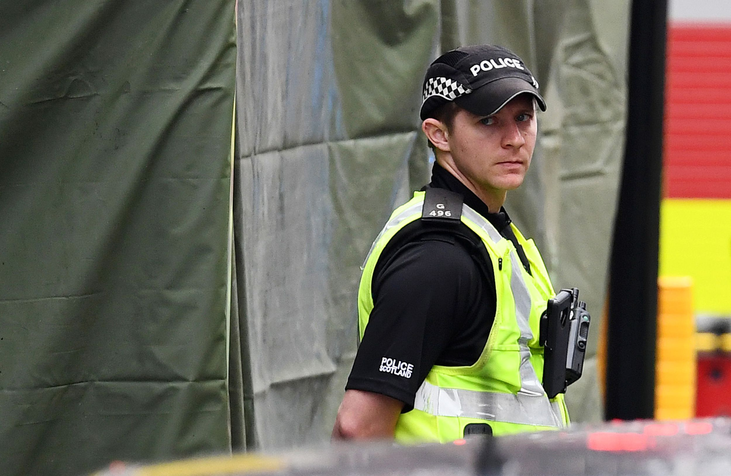 A police officer stands in front of a cordoned off area