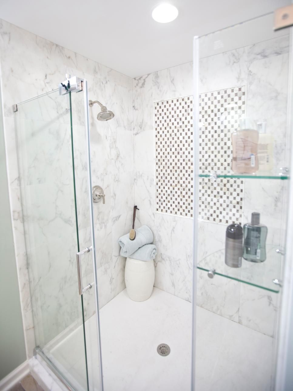 A walk-in shower has built in glass shelves to store shampoo ...