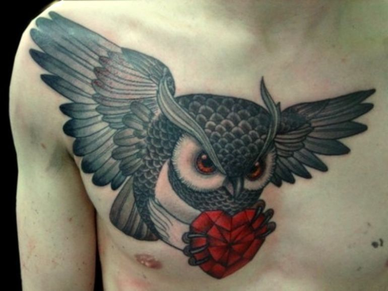 Flying owl with a red heart in its claws tattoo on chest for Owl heart tattoo