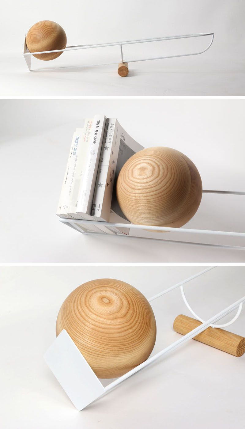 This Bookshelf Design Uses A Wood Ball To Keep Books In Place is part of Unique Home Accessories Shelves - Youngmin Kang has created a modern bookshelf that's designed like a seesaw, with a wooden ball that rolls depending on where the weight on the shelf is