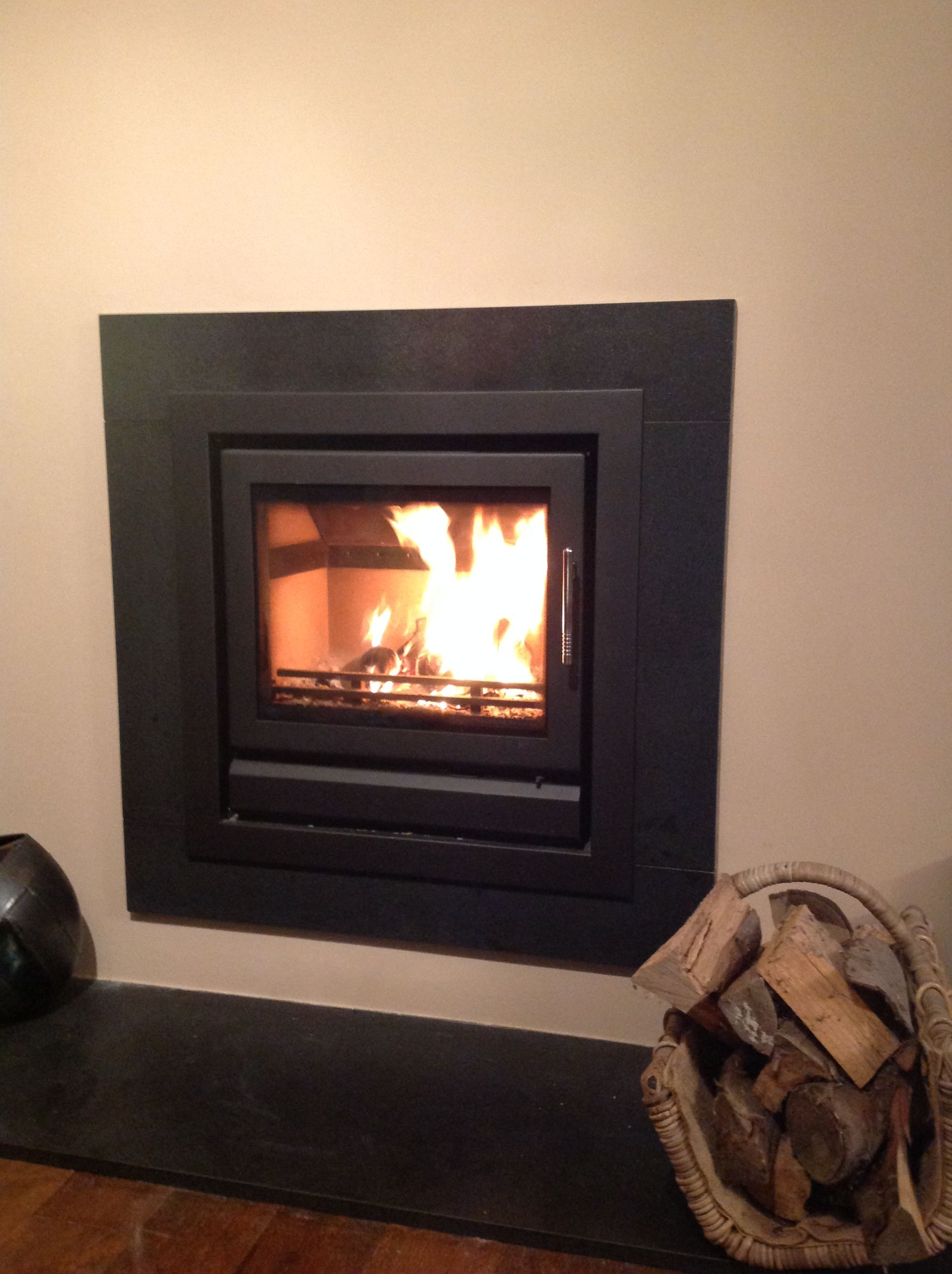 Contemporary hole-in-the-wall log burner which we fitted with a honed granite surround and matching hearth