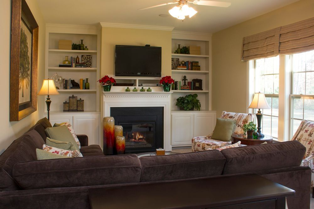 Carteret floorplan cozy family room with mounted tv over fireplace royal oaks homes www Living room layouts with fireplace